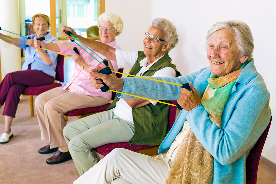 Elderly exercises being performed by 4 women sitting in chairs, with resistance bands.