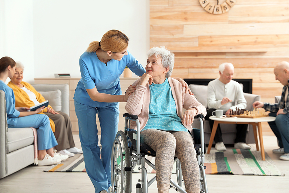 Woman nurse bending down to talk to an elderly patient in a wheelchair.