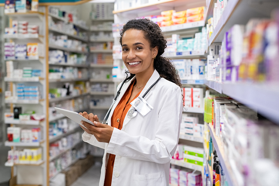Female pharmacist in a pharmacy, smiling and writing on a clipboard.