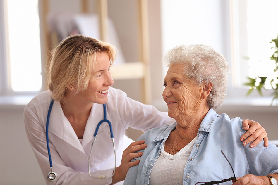 Blonde female doctor discussing various patient services provided by American Care to an elderly woman.
