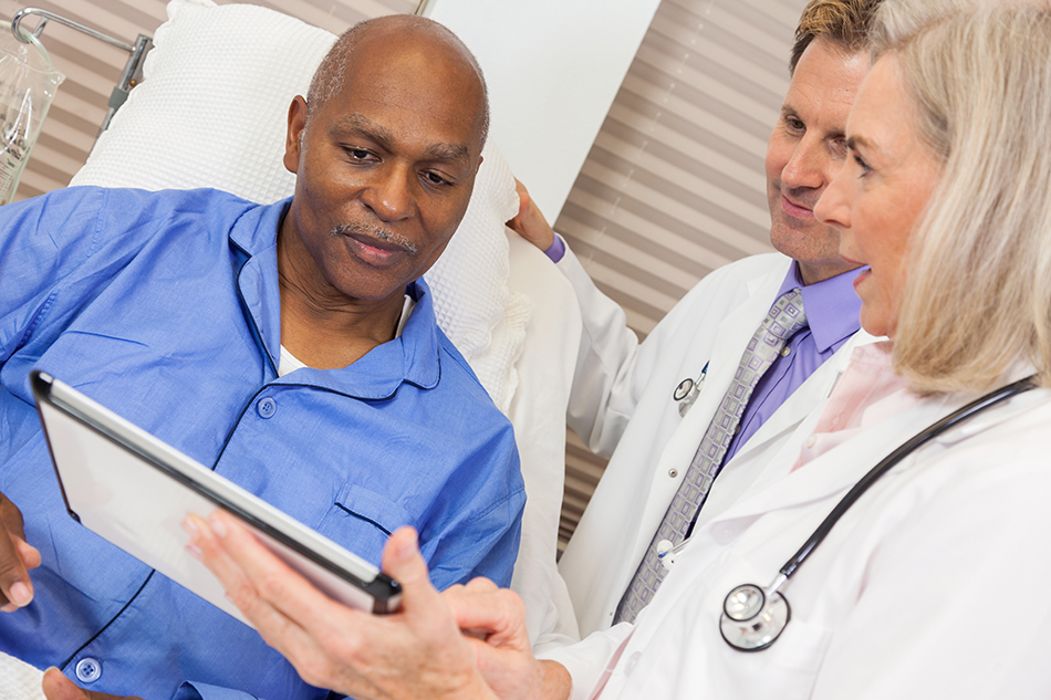 Two primary care doctors discussing test results with an elderly, male patient.