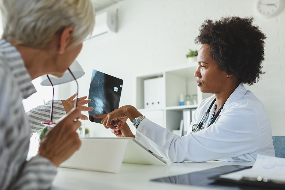Female doctor discussing xray imaging with an elderly female patient.
