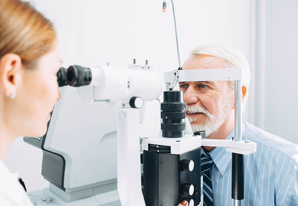 Female optometrist administering an eye exam to an elderly patient.