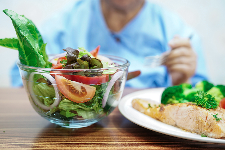Elderly patient eating a salad in a bowl and salmon and broccoli on a plate.