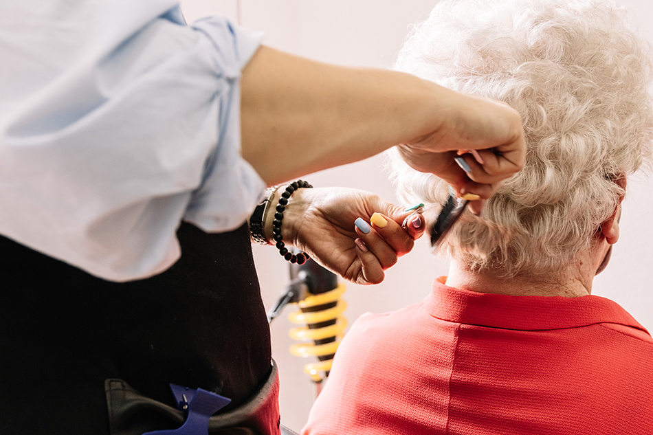 Hairdresser providing cosmetology services by combing an elderly woman's hair.
