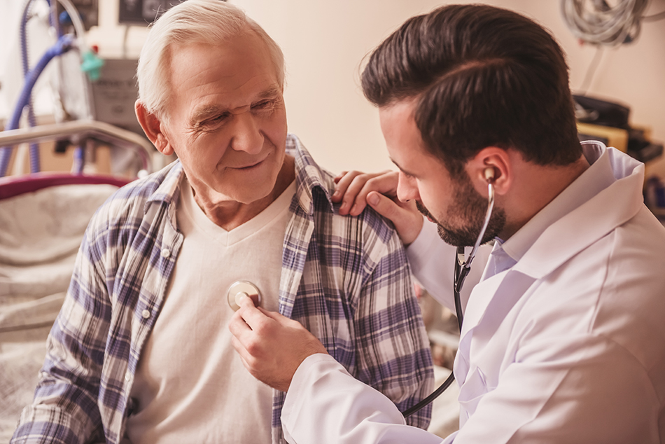 Male doctor holding a stethoscope to an elderly man's chest.