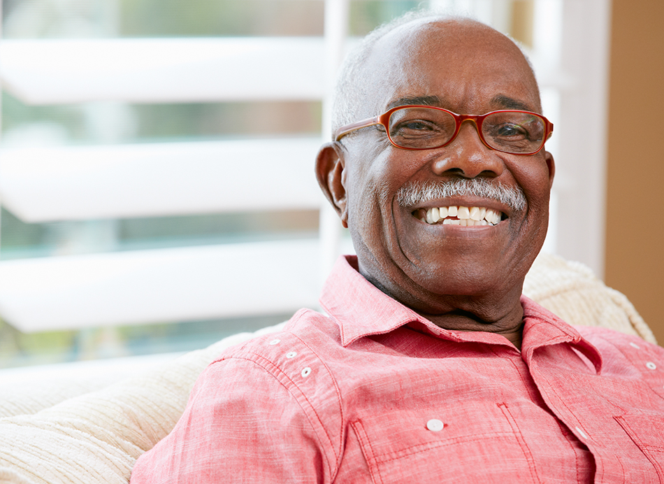 Senior man with a red shirt and red glasses, smiling.