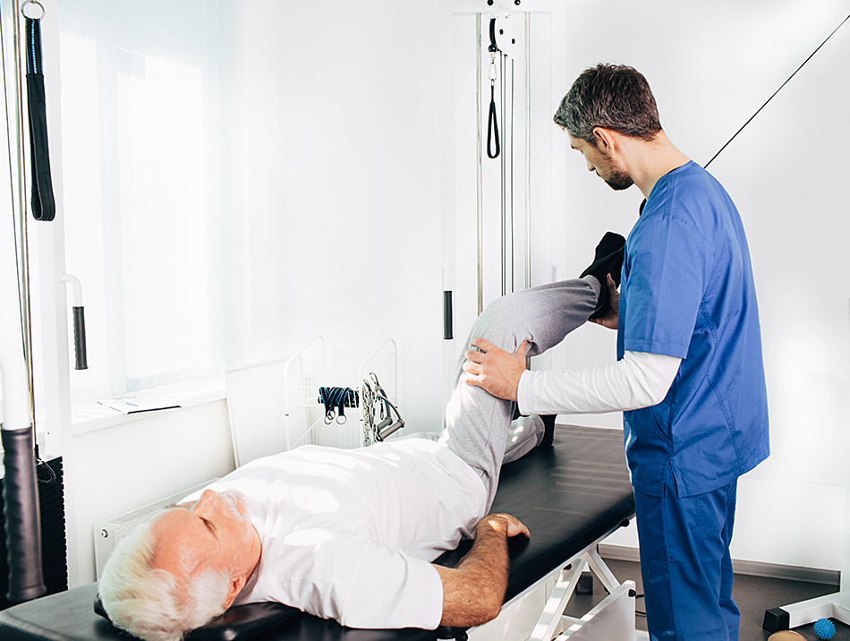 Elderly man laying on a table with a male nurse stretching his legs to help with pain management.