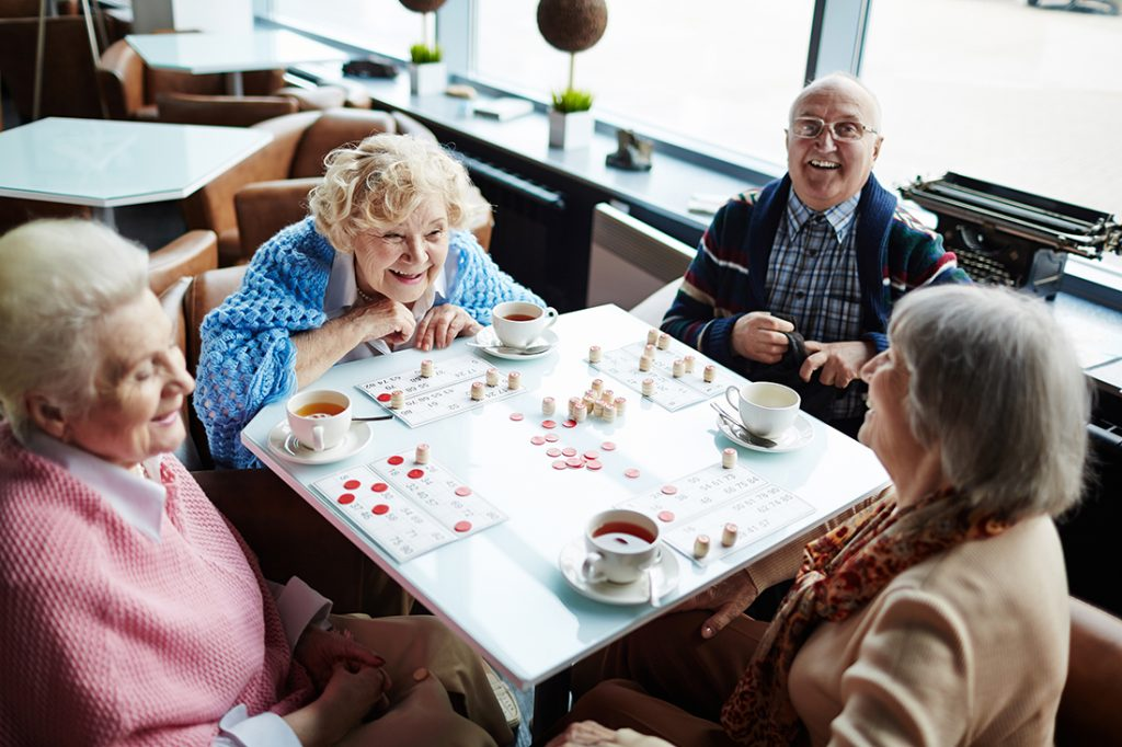Elderly men and women smiling, playing a game of bingo on a white table.