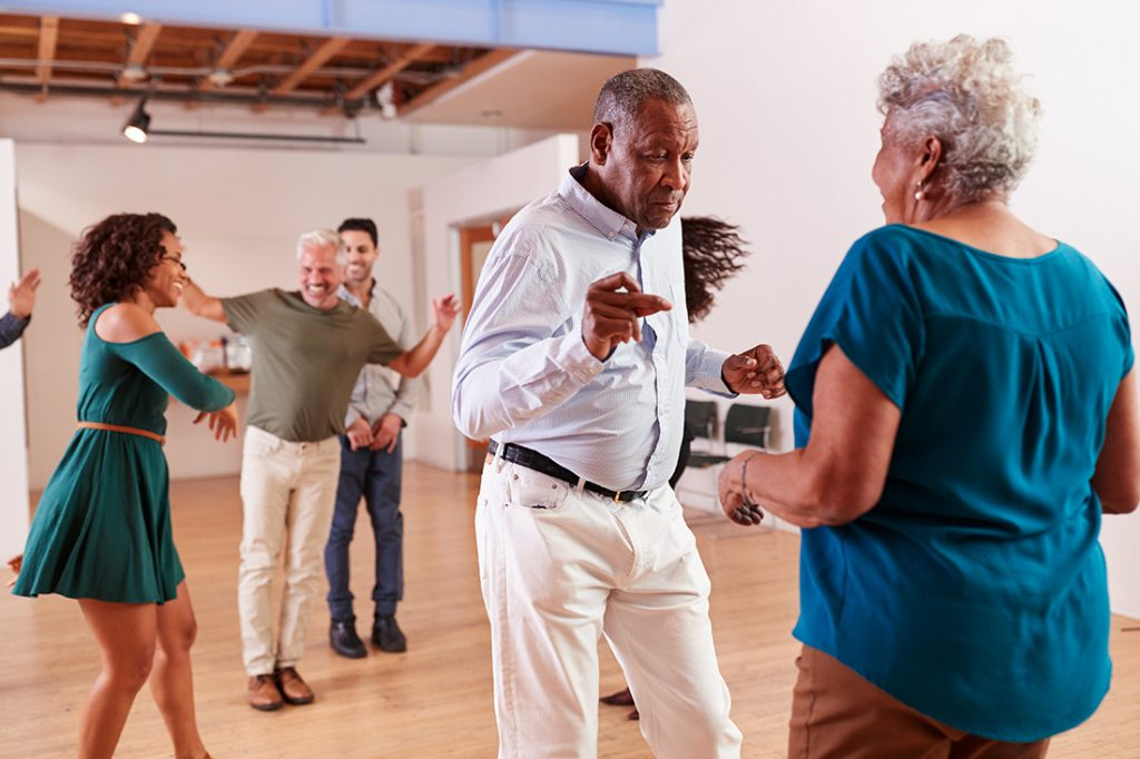 Elderly man and woman participating in a dance class, with other seniors in the background.