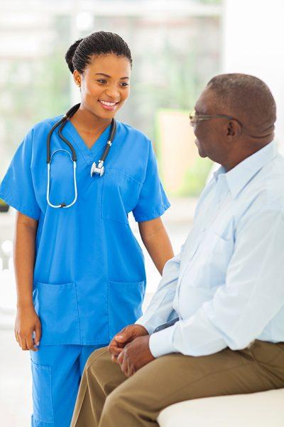 Nurse in blue scrubs talking to an elderly, male patient.