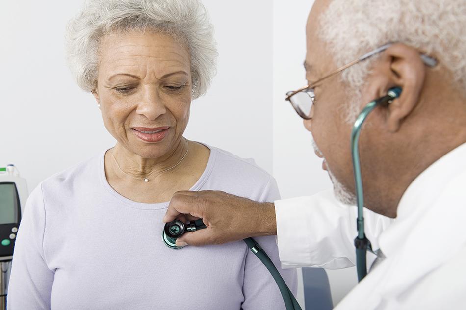 Elderly woman having her heart listened to by an elderly, male doctor.