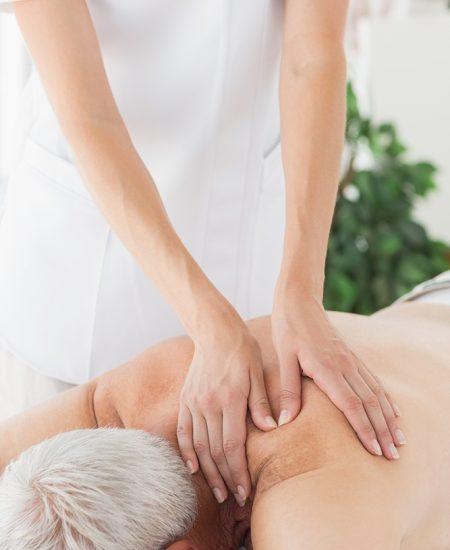 Massage therapist massaging back of senior man